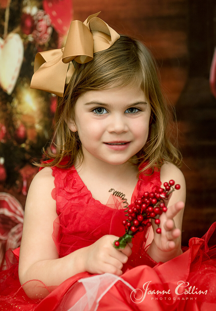 Childrens Christmas Photoshoot 3 year old girl by christmas tree with party dress and gold bow